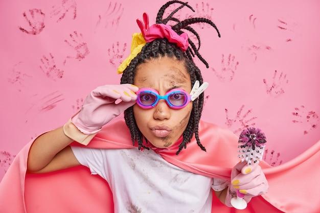 Skrupellose superfrau, die bereit ist, die welt vor schmutz zu retten, reinigt die toilette mit einer bürste, die aufmerksam durch die brille schaut, hat ein schmutziges gesicht in einem superheldenkostüm, das über einer rosa wand isoliert ist
