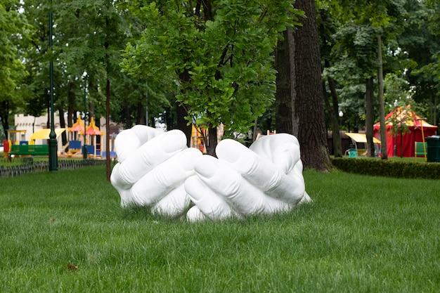 Skulptur im park, menschliche hände halten einen baum. ein denkmal für freundlichkeit und fürsorge für die natur.