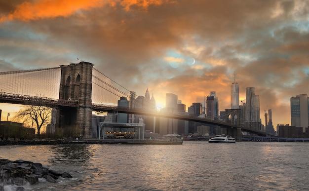 Skyline von new york von brooklyn-brücke bei sonnenuntergang mit mond