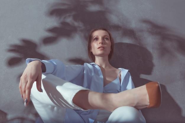 Slawische intelligente junge frau, die an der grauen studiowand im pflanzenschatten sitzt und stilvolle blaue baumwollbluse, weiße jeans und braune pumps trägt.