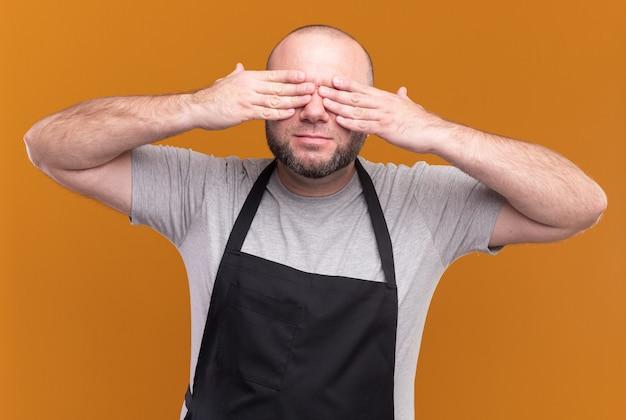 Slawischer männlicher friseur mittleren alters in einheitlich bedeckten augen mit auf orange wand isolierten händen
