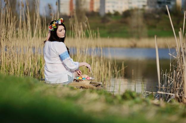 Slawisches mädchen im ukrainischen hemd, das auf der brücke mit ostern sitzt