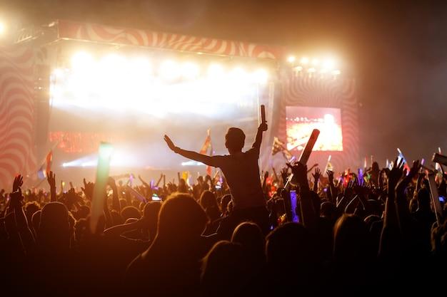 Slhouette des jungen mannes auf konzertfestivalereignis