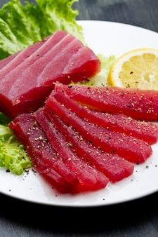 Slicesfield mit rohem sashimi des roten thunfischs auf weißem teller auf hölzernem backgr