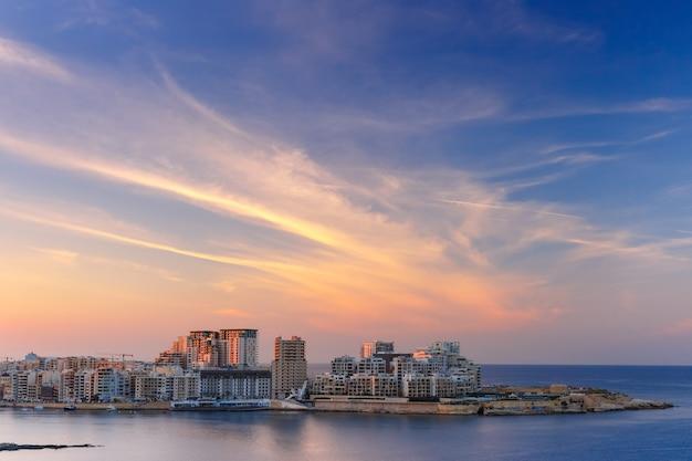 Sliema, ein bedeutendes wohn- und geschäftsviertel und ein zentrum für einkaufsmöglichkeiten, restaurants und cafés in malta. skyline in strand und tigne point bei sonnenuntergang von valletta aus gesehen