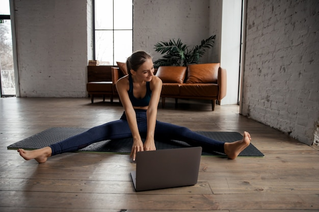Slim fit frau, die zu hause yoga praktiziert und den körper mit einem laptop für online-kurse oder virtuelle tutorials streckt. hochwertiges foto
