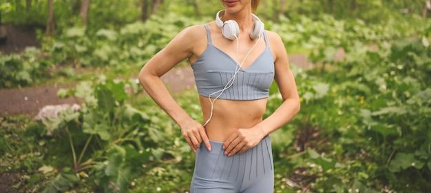 Slim fit mädchen in blauer sportbekleidung mit großen weißen kopfhörern, die sport und fitness im sommerpark draußen tun