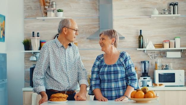 Slow-motion-portret eines älteren paares in der küche, das sich anlächelt und in die kamera schaut. fröhliche frau und ehemann.