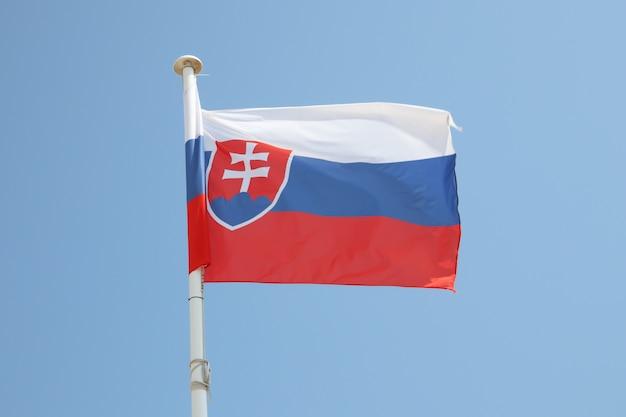 Slowakei-flagge auf einer matte im wind und im blauen himmel