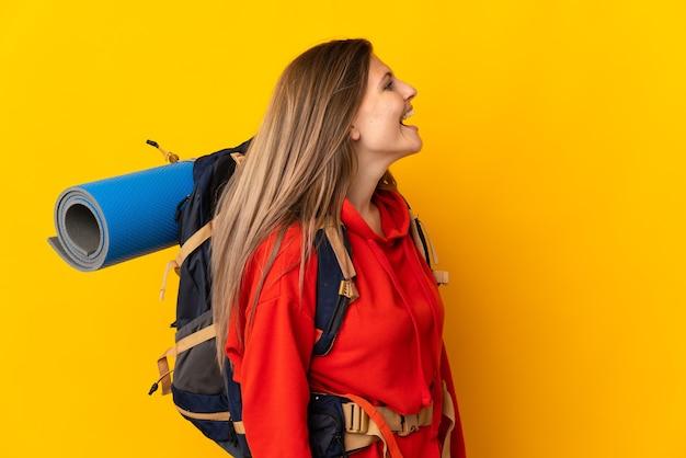 Slowakische bergsteigerfrau mit einem großen rucksack lokalisiert auf gelbem hintergrund, der in seitlicher position lacht
