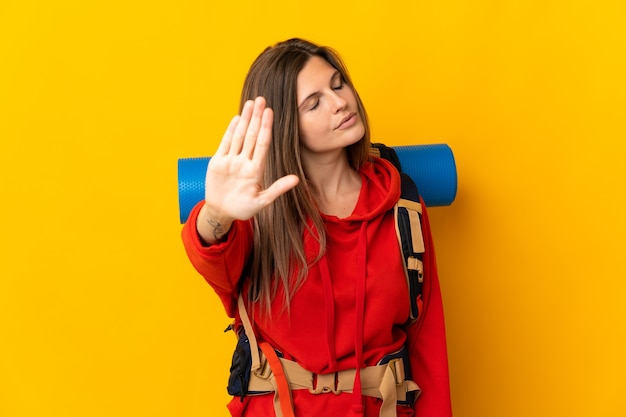 Slowakische bergsteigerfrau mit einem großen rucksack lokalisiert auf gelber wand, die stoppgeste macht und enttäuscht