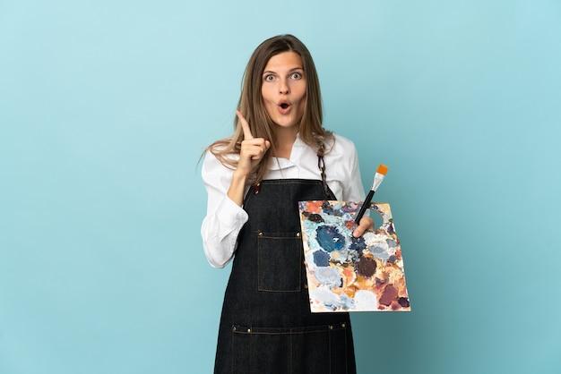 Slowakische frau des jungen künstlers isoliert auf blauer wand, die beabsichtigt, die lösung zu verwirklichen, während sie einen finger anhebt