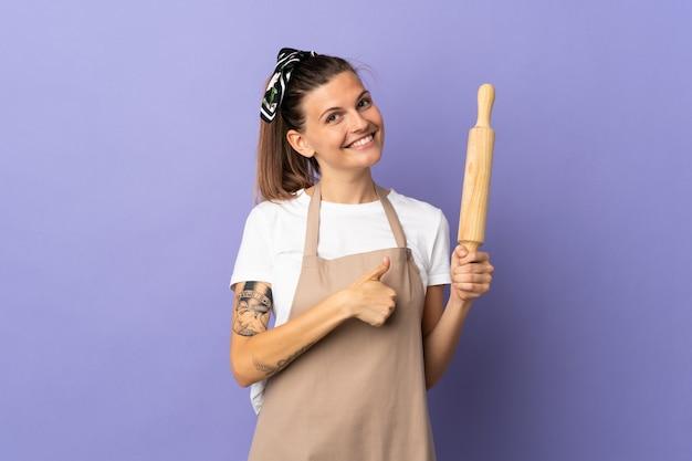 Slowakische frau des kochers lokalisiert auf lila hintergrund, der eine daumen hoch geste gibt