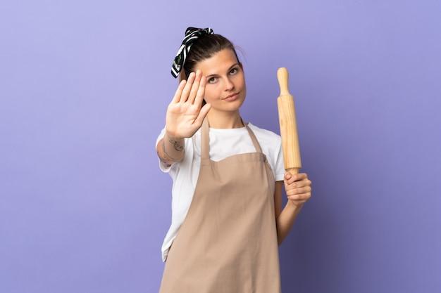 Slowakische frau des kochers lokalisiert auf lila wand, die stoppgeste macht