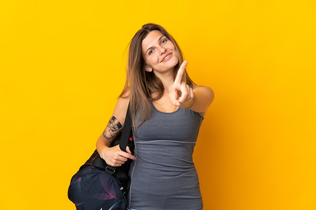 Slowakische sportfrau mit sporttasche lokalisiert auf gelber wand, die einen finger zeigt und hebt