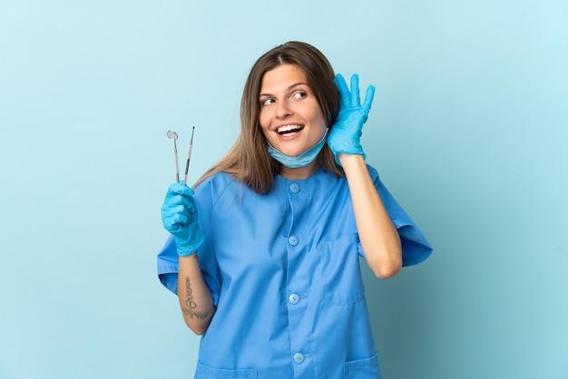 Slowakischer zahnarzt, der werkzeuge hält, die auf blaue wand lokalisiert werden, die etwas hört, indem man hand auf das ohr legt