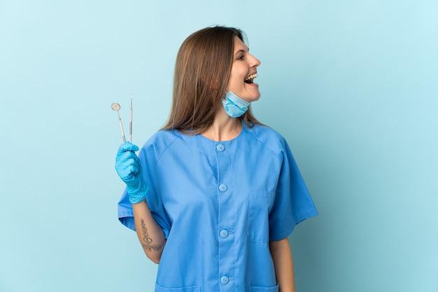 Slowakischer zahnarzt, der werkzeuge hält, die auf blauem hintergrund lokalisiert werden, der in seitlicher position lacht