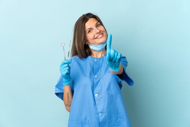 Slowakischer zahnarzt, der werkzeuge hält, die auf blauer wand lokalisiert werden, die einen finger zeigt und anhebt