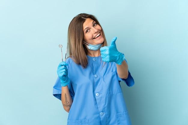 Slowakischer zahnarzt hält werkzeuge isoliert auf blauer wand mit daumen hoch, weil etwas gutes passiert ist