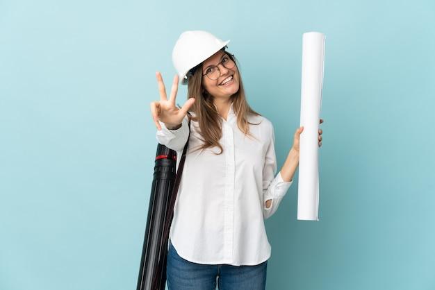 Slowakisches architektenmädchen, das blaupausen auf blauem hintergrund glücklich hält und drei mit den fingern zählt