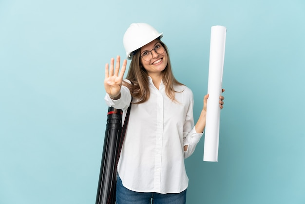 Slowakisches architektenmädchen, das blaupausen lokalisiert auf blauer wand glücklich hält und vier mit den fingern zählt