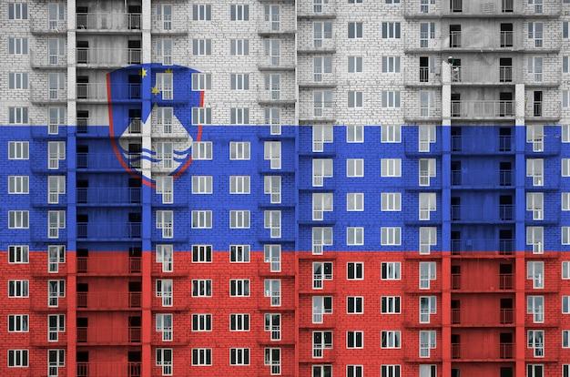 Slowenische flagge in farben auf mehrstöckigem wohngebäude im bau dargestellt.