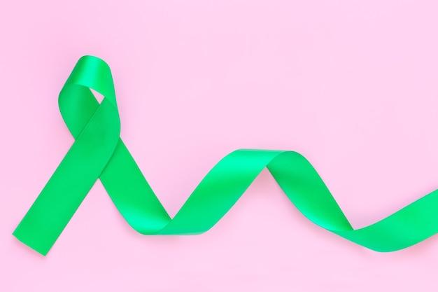 Smaragdgrünes lockiges band auf pastellrosa oberfläche