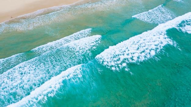 Smaragdmeer und kleiner tourist, der auf dem sandstrand am surinstrand, phuket, thailand liegt