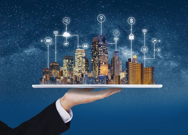 Smart city, gebäudetechnik und immobiliengeschäft. geschäftsmann, der digitale tablette mit gebäudehologramm- und -anwendungsprogrammierschnittstellentechnologie hält