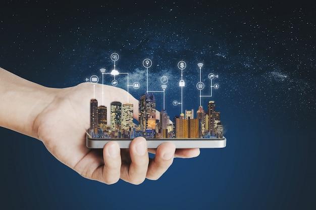 Smart city, gebäudetechnik und mobile anwendungstechnik. hand, die intelligentes mobiltelefon mit gebäudehologramm- und -anwendungsprogrammierschnittstellentechnologie hält