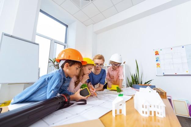 Smart city modellieren. kinder mit hellen helmen konstruieren und modellieren mit dem lehrer eine intelligente stadt