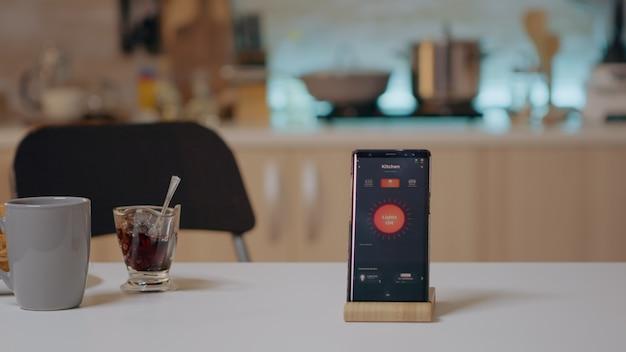 Smart home-anwendung auf dem telefon auf dem küchentisch im leeren hausautomationssystem platziert und schaltet das licht ein. mobil mit kabelloser lichtsteuerung, hightech zur überwachung der stromeffizienz