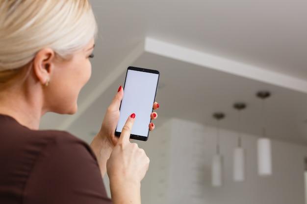Smart home: frau steuert lichter mit app auf ihrem handy
