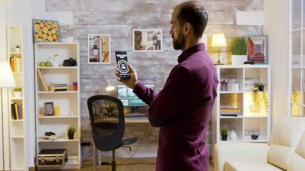 Smart-house-anwendung mit einem mann, der das licht über einen sprachbefehl auf seinem telefon einschaltet