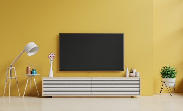 Smart tv an der gelben wand im wohnzimmer und stehlampe, minimales design