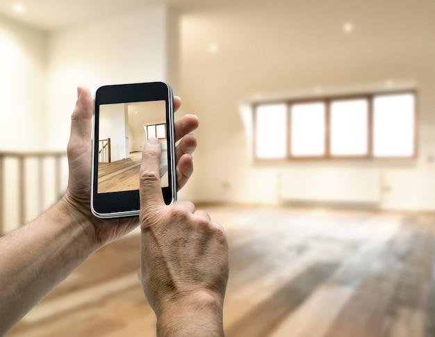 Smarthphone mit der mannhand, die foto im modernen dachboden macht