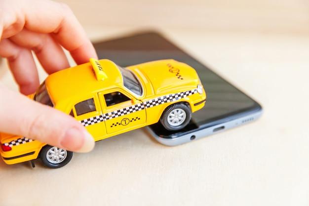 Smartphone-anwendung des taxidienstes für die online-suche nach anruf- und buchungskonzepten. hand, die gelbes spielzeugauto taxi cab auf leerem bildschirm des smartphones auf tisch hält. taxisymbol.