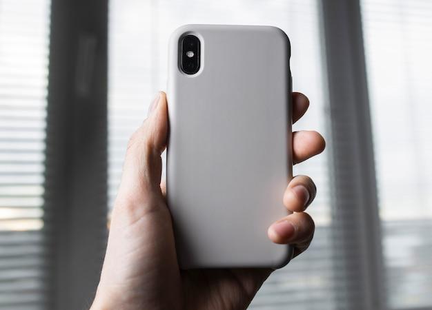 Smartphone auf dem unscharfen raum des fensters in einer weißen plastikgehäuse-rückansicht. smartphone in der hand des mannes. vorlage der telefonhülle