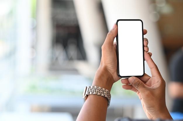 Smartphone auf den händen des mannes mit leerem schirm und bokeh auf unschärferaum