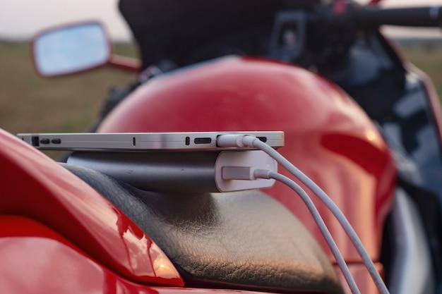 Smartphone auf einem motorrad und powerbank lädt das telefon vor der kulisse der natur auf.