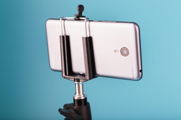 Smartphone auf einem stativ als foto-video-kamera auf blauem hintergrund. nehmen sie videos und fotos für ihr blog auf.