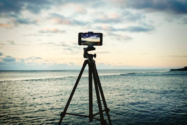 Smartphone auf stativ, das sonnenaufgang des seestücks erfasst. mobiles fotografie- oder videokonzept.
