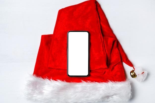 Smartphone auf weihnachtsmann mütze