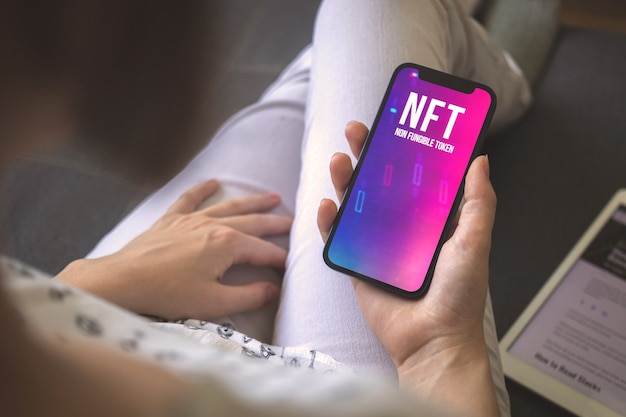 Smartphone-bildschirm mit nft-logo in der frauenhand. konzept der kryptokunst und technologiefoto