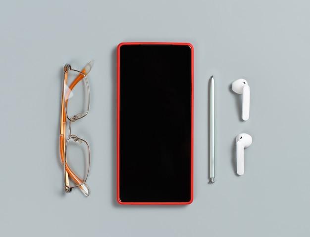 Smartphone, brille, notizstift und weiße drahtlose kopfhörer draufsicht auf grauem hintergrund