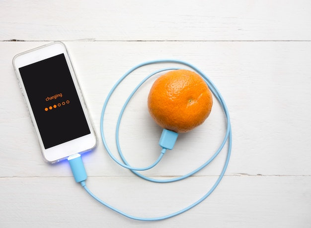 Smartphone, das batterie von der orange frucht auflädt