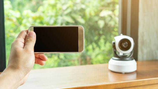 Smartphone, das mit der sicherheits-ip-kamera auf einem holztisch verbindet.