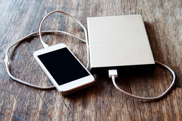 Smartphone, das mit energiebank auf hölzernem hintergrund auflädt