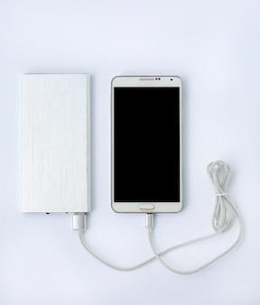 Smartphone, das mit energiebank auf weißem hintergrund auflädt