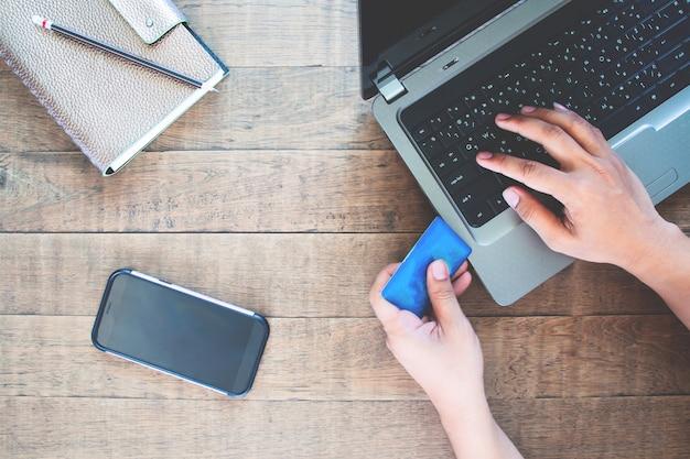 Smartphone des leeren bildschirms für anwendung verspotten oben mit dem mann, der kreditkarte und laptop-computer verwendet